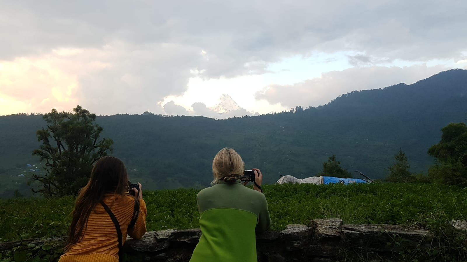Two girls taking photos of mountains